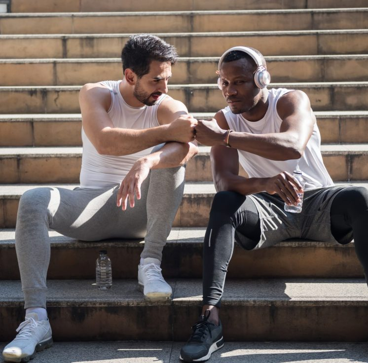 Young American and black African friends giving fists bump on staircase of skywalk after jogging or running . Sport and healthy lifestyle. Black lives matter and antiracism with friendship concept.